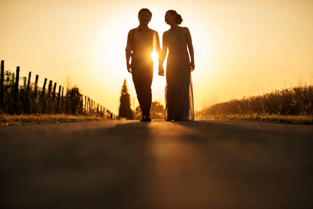 bride and groom holding hands walking towards camera during sunset