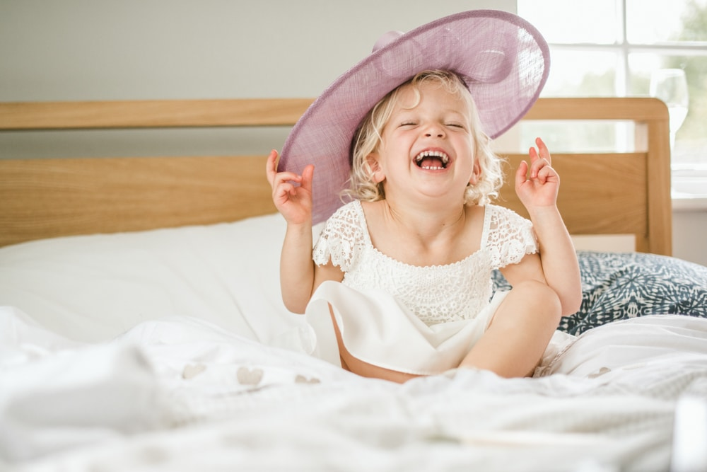flower girl laughing with large pink hat
