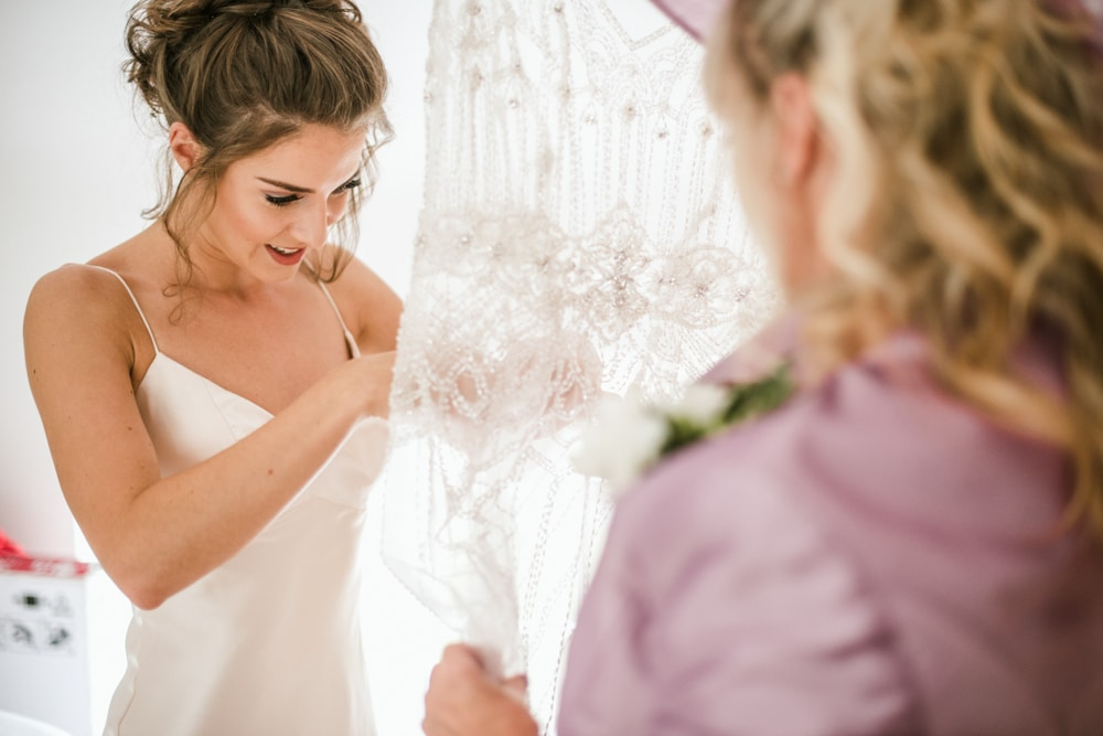 bride getting into lace dress