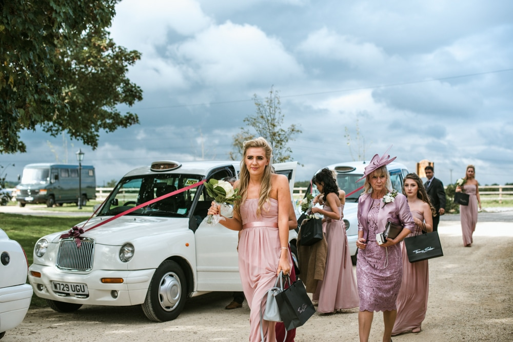 Bridesmaids arriving at Micklefield Hall in white taxis