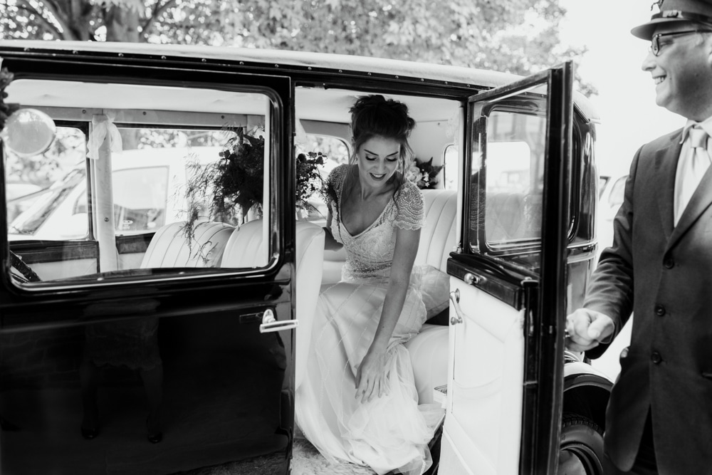 bride getting out vintage wedding car
