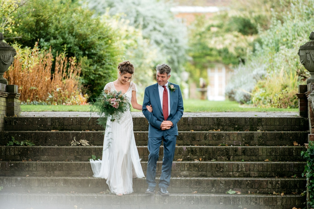 bride walking down steps at Micklefield Hall with her father