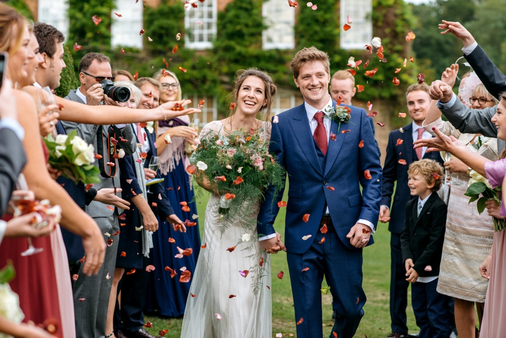 bride and groom walking through petal confetti