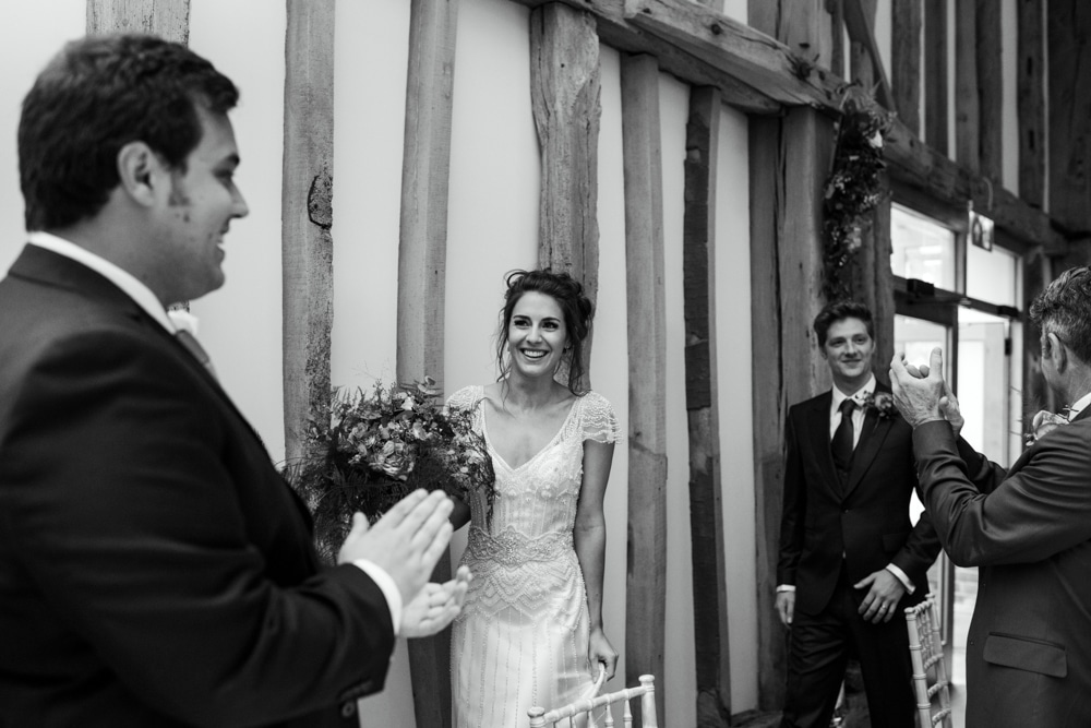 bride and groom walking into barn