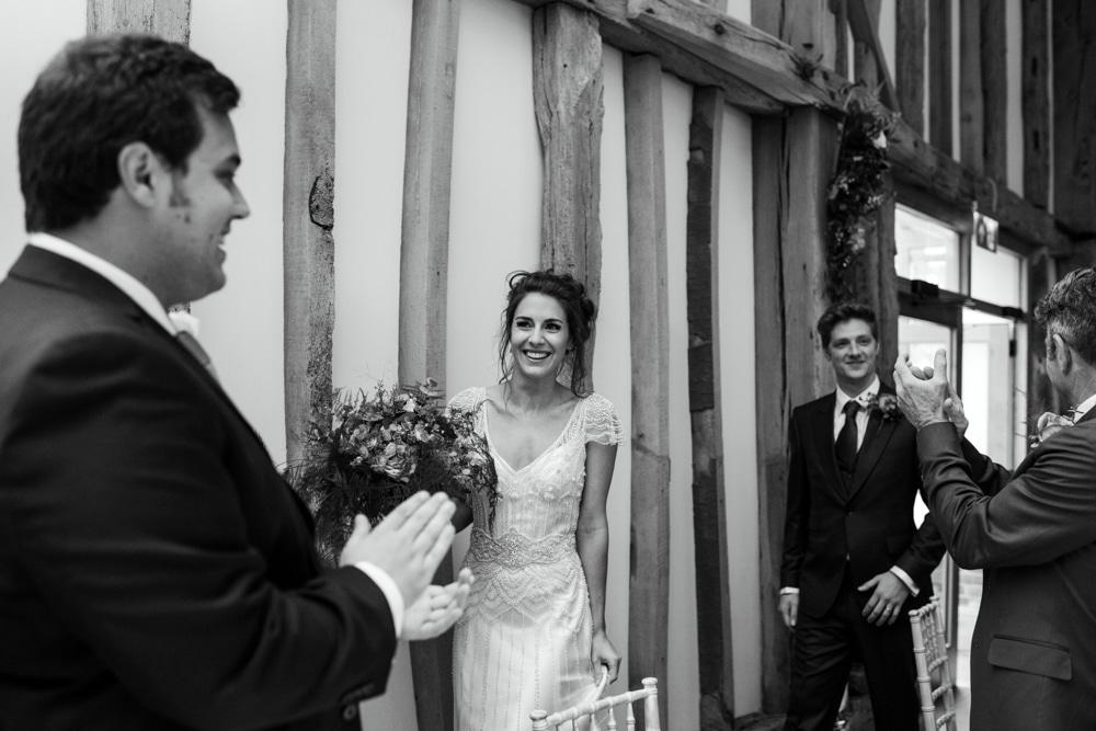 bride and groom walking into barn