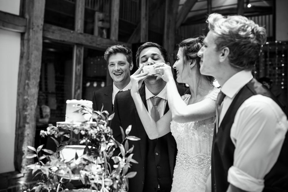 bride feeding cake to bestman