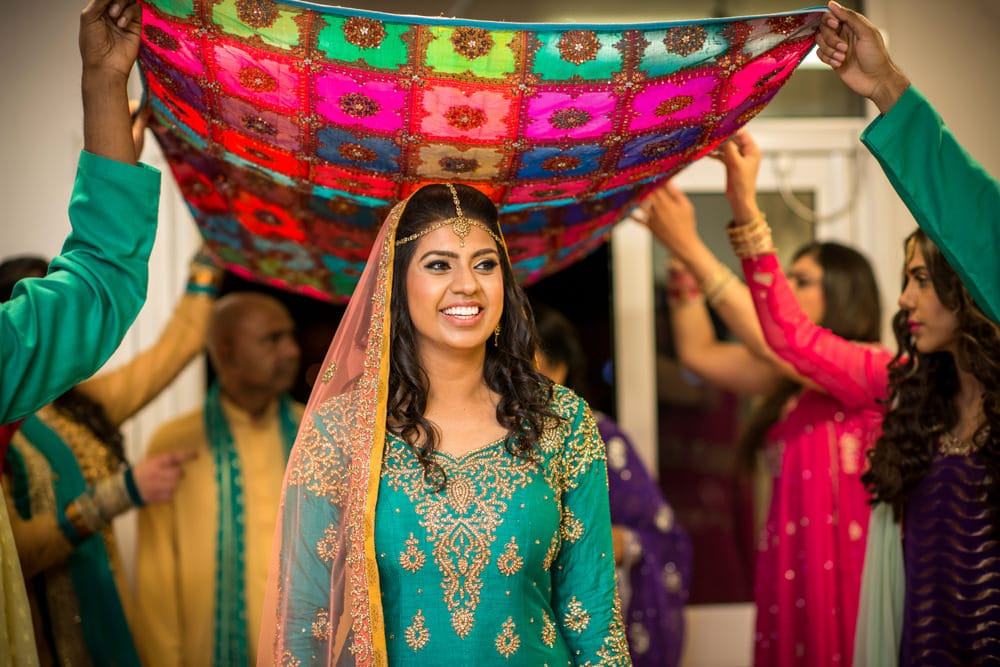 bride walking under colourful mend blanket