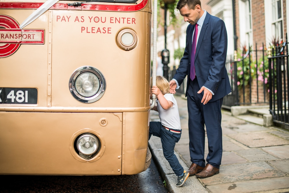 little boy getting onto vintage bus