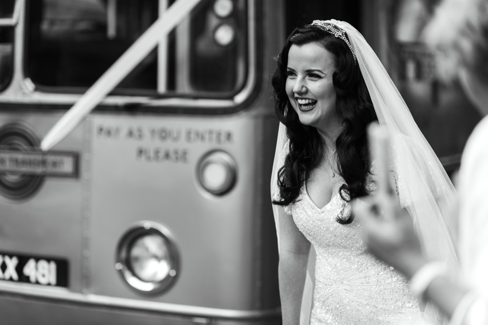 bride in front of vintage wedding bus