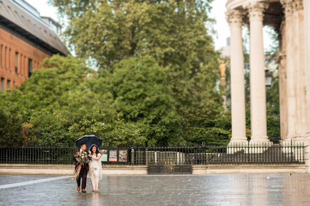 bride and groom walking outside St Pauls