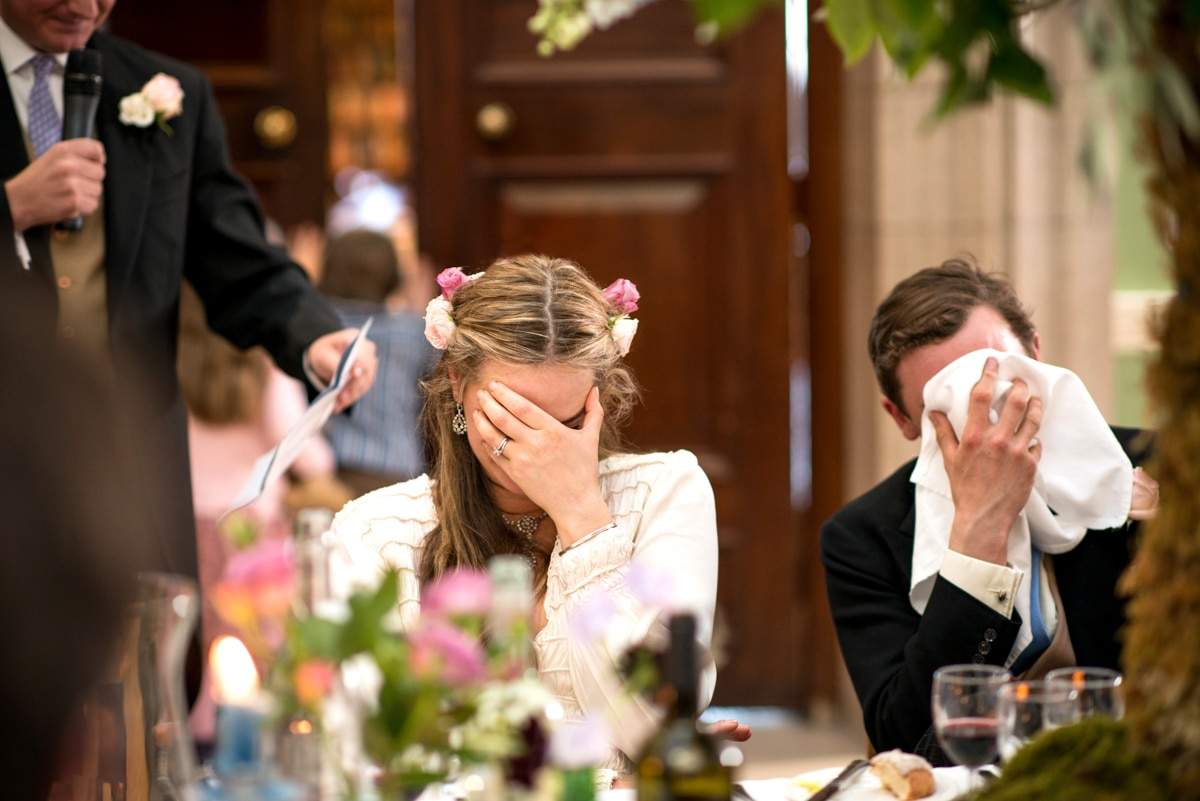bride and groom hiding their faces in embarrassment during the speeches