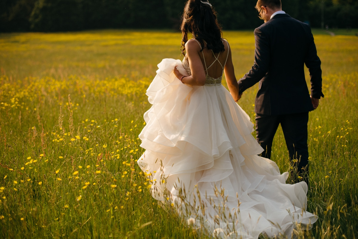 bride and groom walking through field of yellow flowers, Botleys Mansion