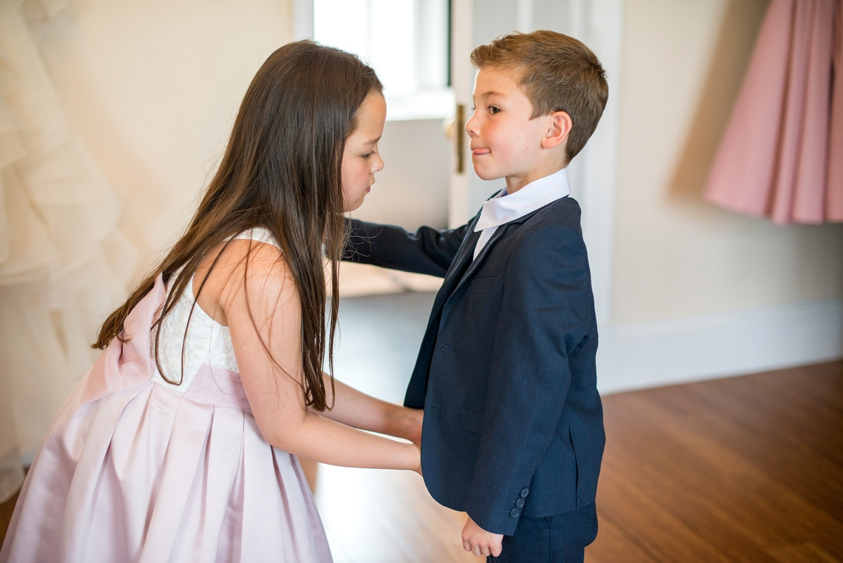 pageboy receiving help dressing from flower girl