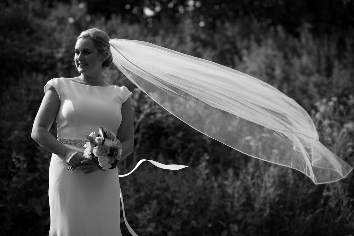bride with veil blowing in wid
