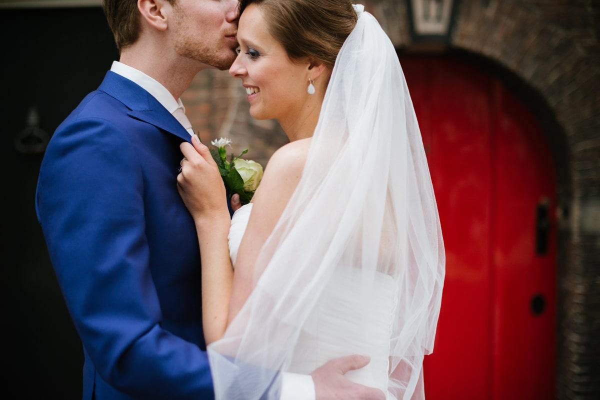 bride and groom kissing in front of red door