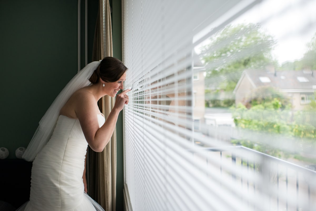 bride looking out of window at groom arriving