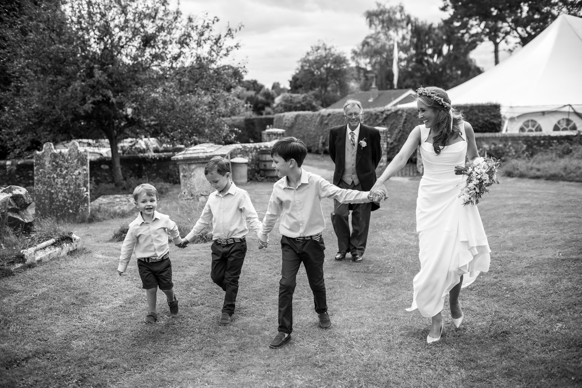 Bride walking to church with 3 pageboys