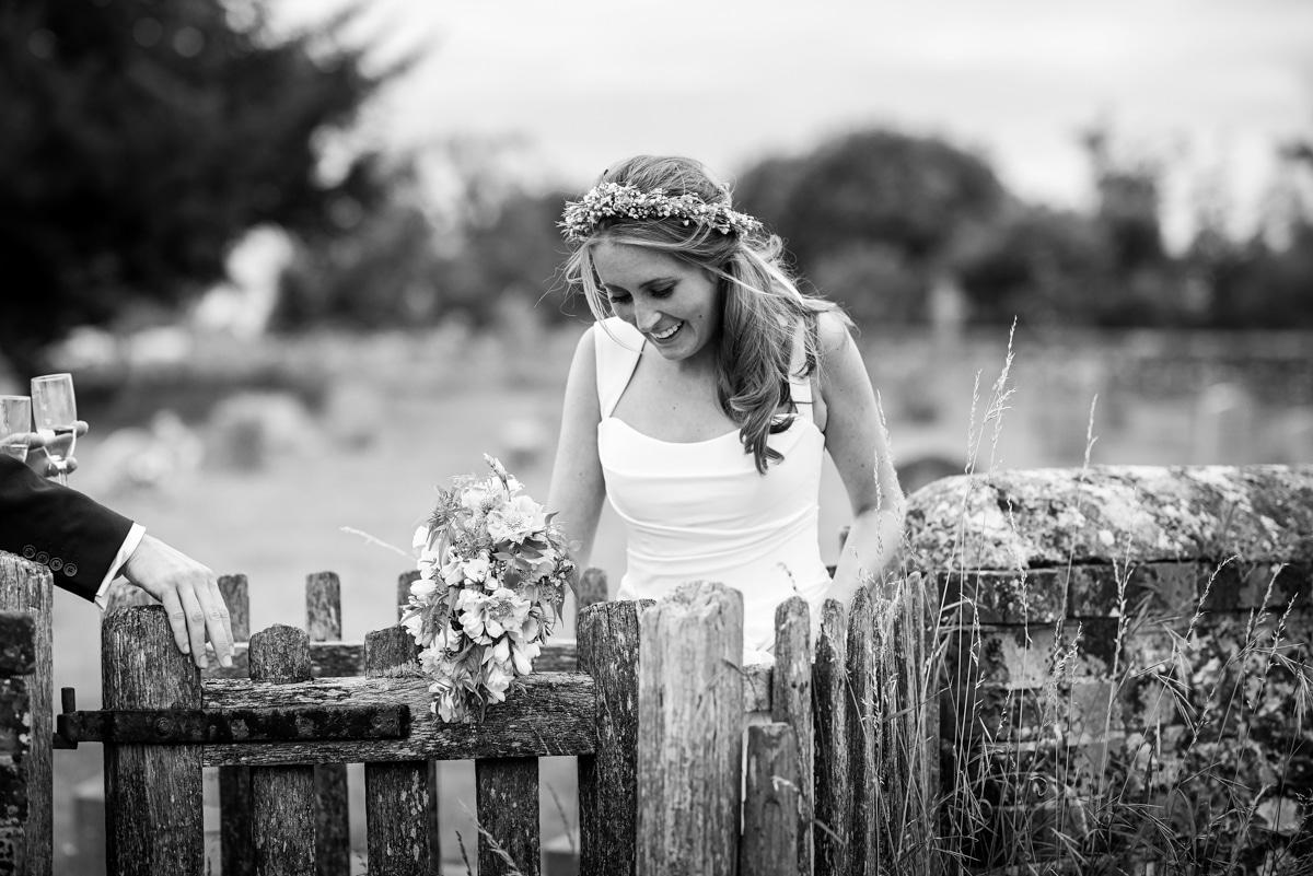 Bride walking through kissing gate, country wedding