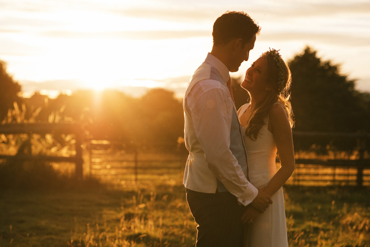 Golden light portrait of bride and groom in field