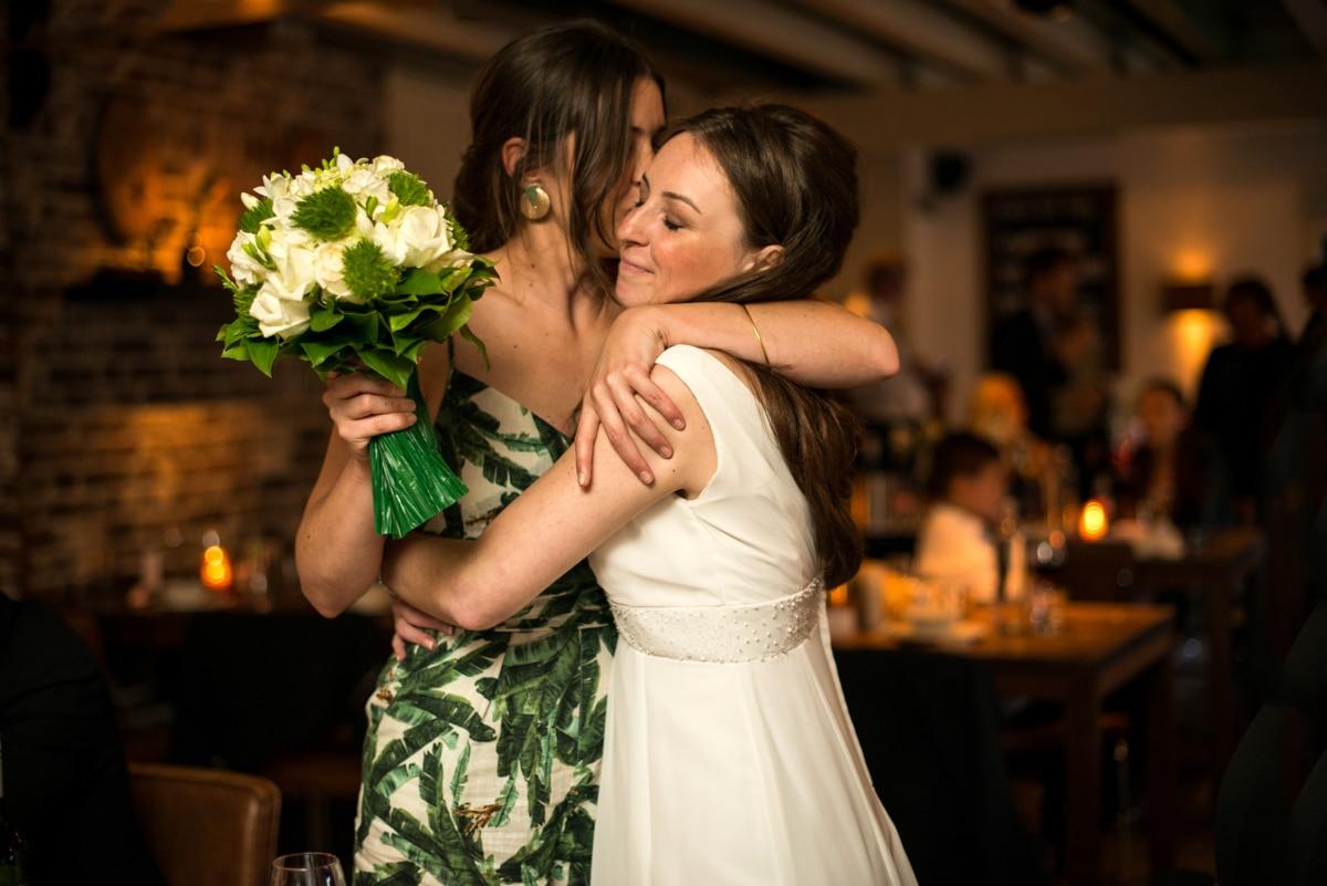 Bride hugging her best friend at wedding