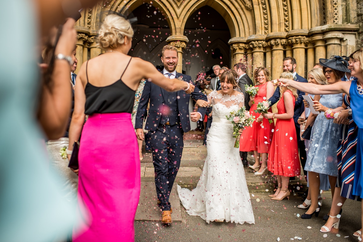 bride and groom exiting church, confetti line