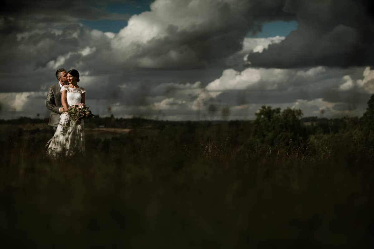 bride and groom portrait in field in France, dramatic light