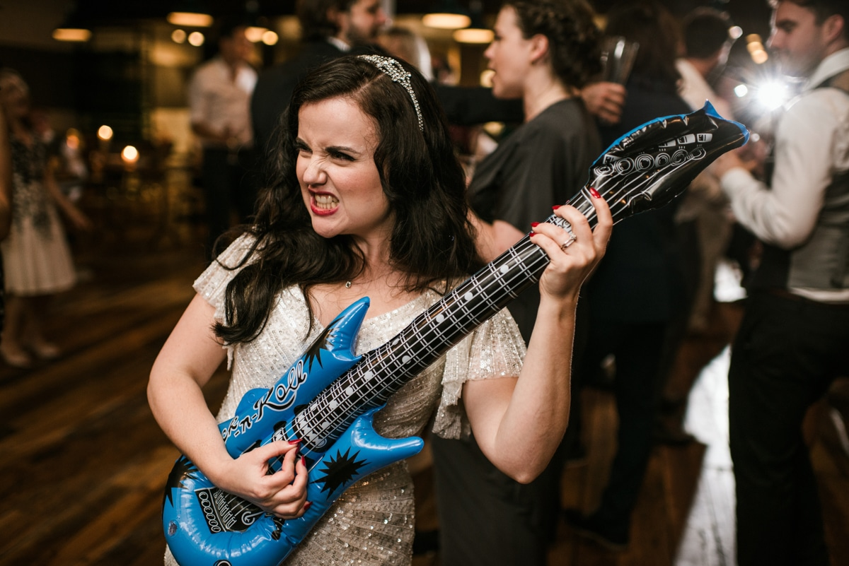 bride playing a blow up guitar, London wedding at the Happenstance