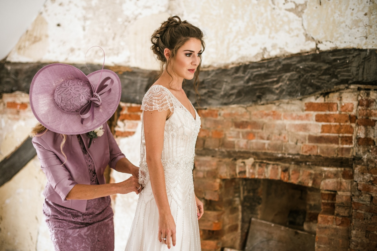 mother helping bride into wedding dress