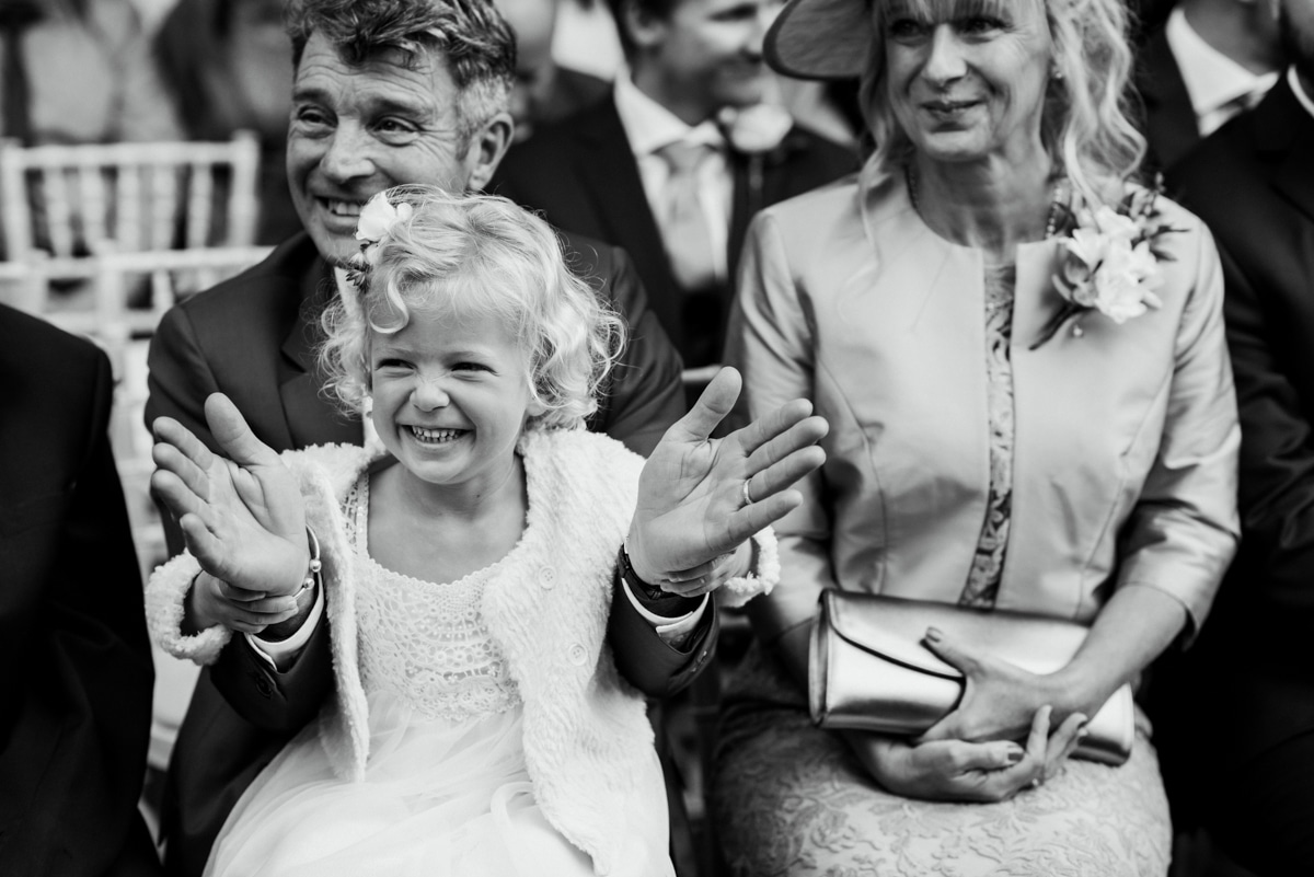 Flower girl clapping with granddad during ceremony