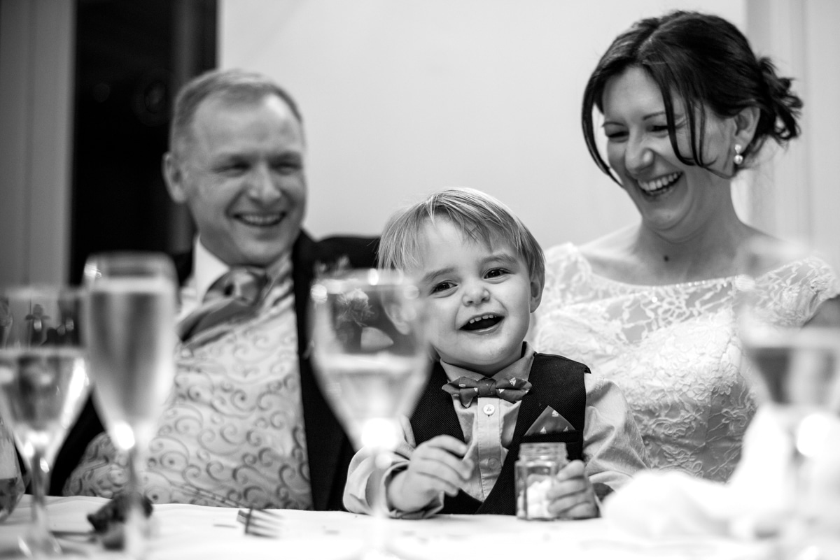 Bride and groom with son during wedding speeches