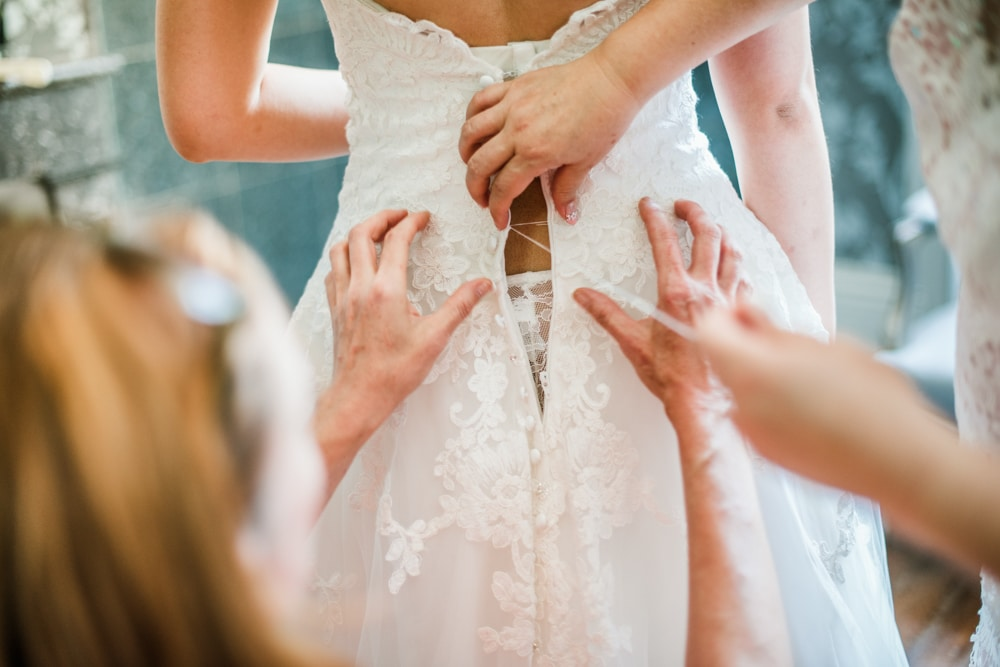 bride getting sewn into broken wedding dress
