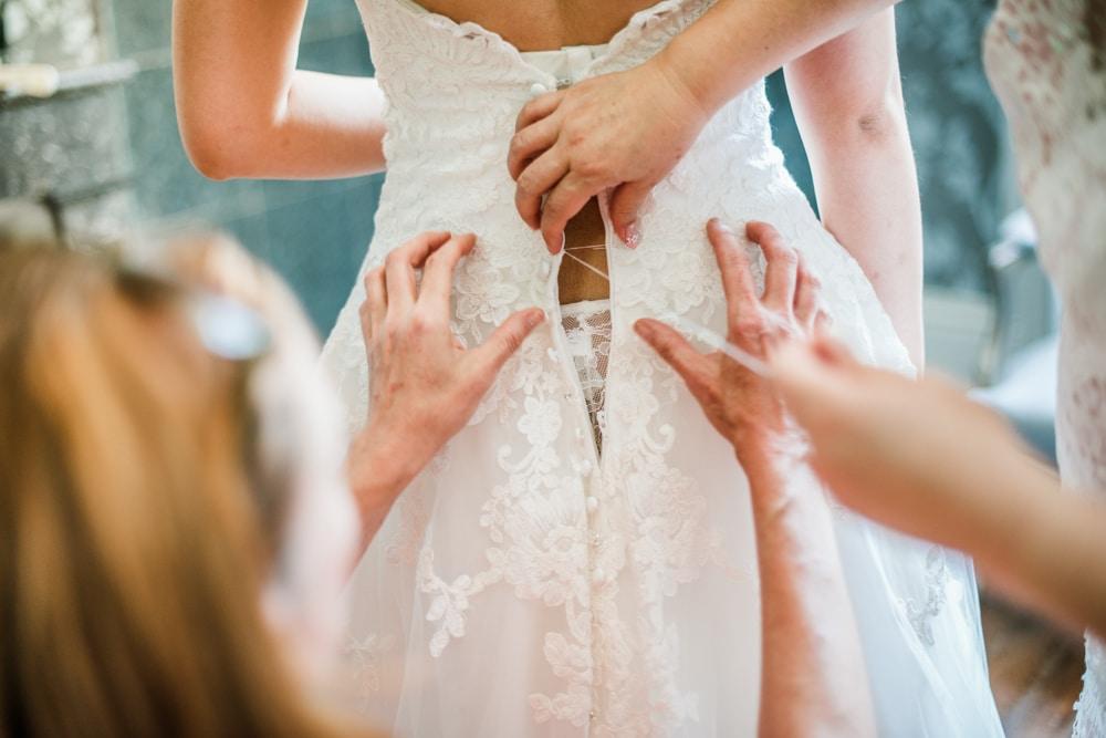 bride getting sewn into broken wedding dress