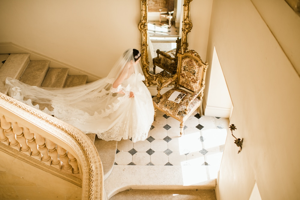 Bride walking down stairs at Chateau De Laurantie