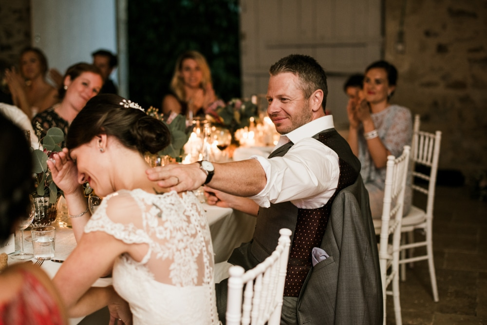 groom with hand on brides back during speeches
