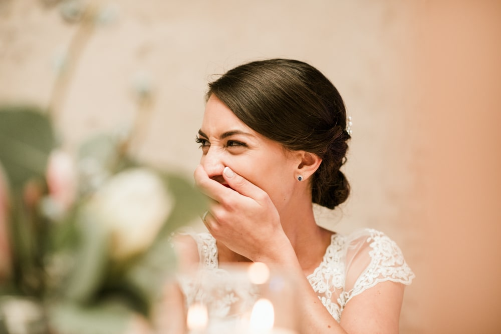 bride laughing with hand over her mouth at wedding