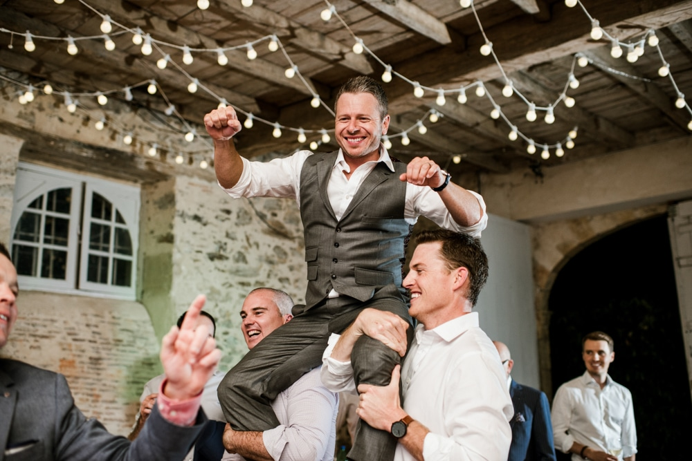 groom on guests shoulders during party