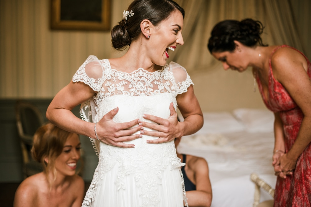 bride getting help from bridesmaids into her wedding dress