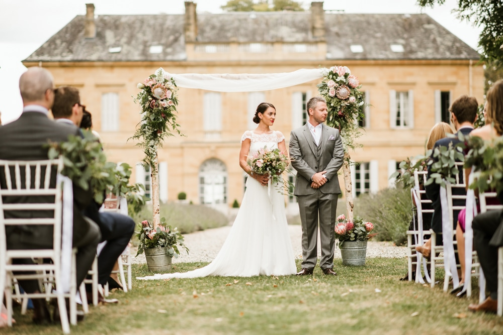bride and groom in front of Chateau La Durantie during the ceremony