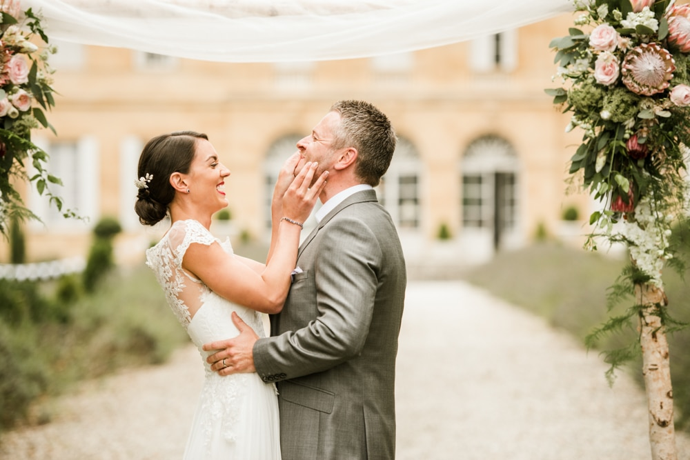 bride wiping lipstick away from grooms lips