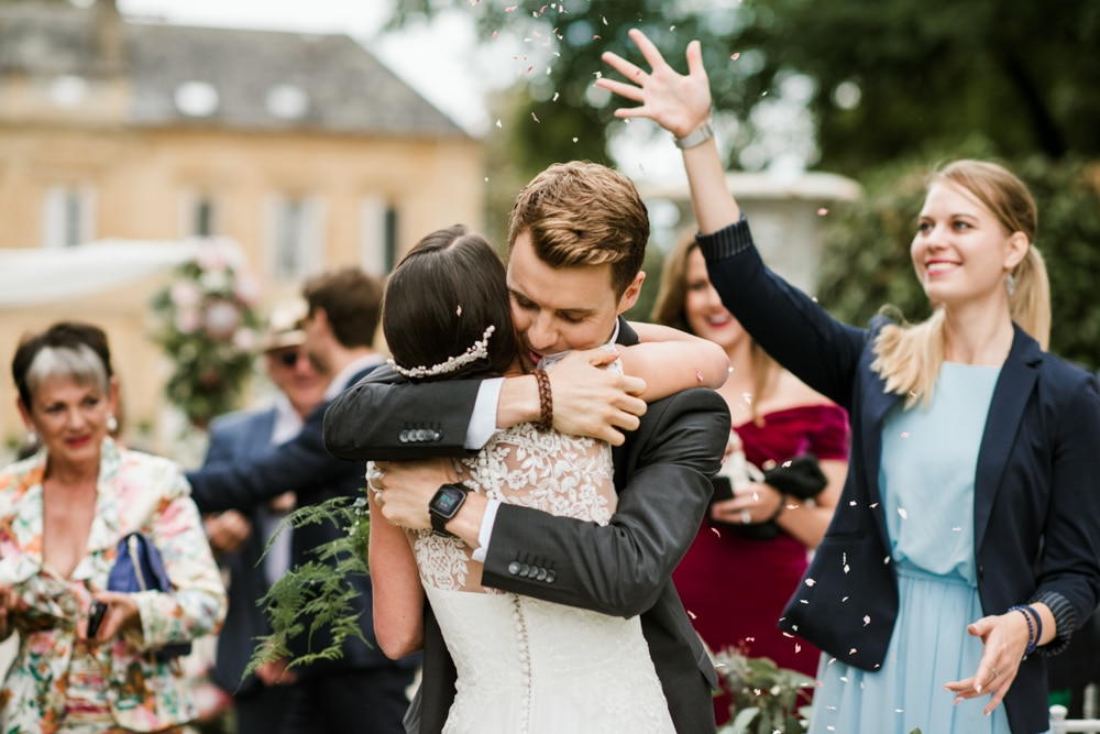 celebratory hugs from guests after wedding ceremony