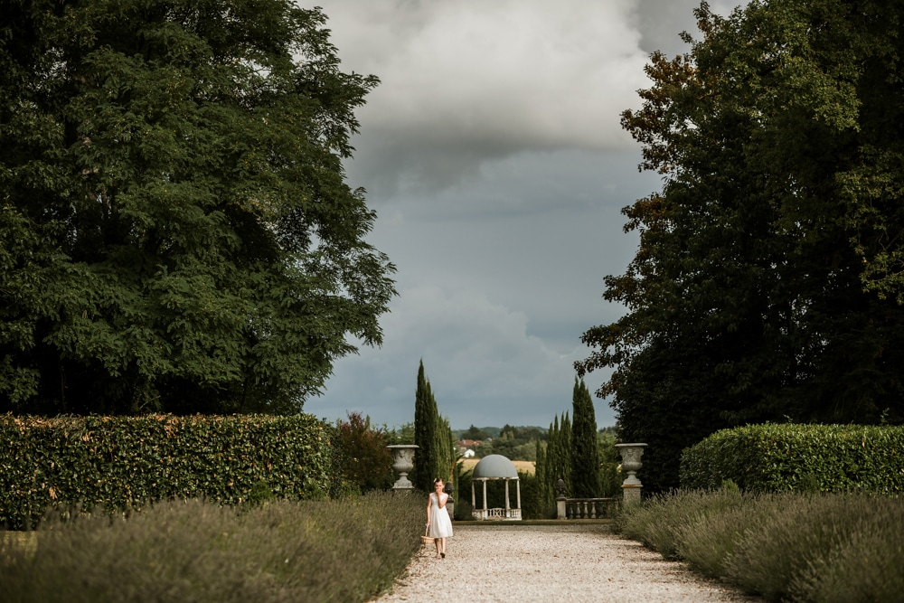 flower girl walking alone in the gardens of Chateau La Durantie