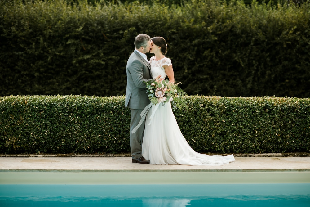 bride and groom kiss by pool