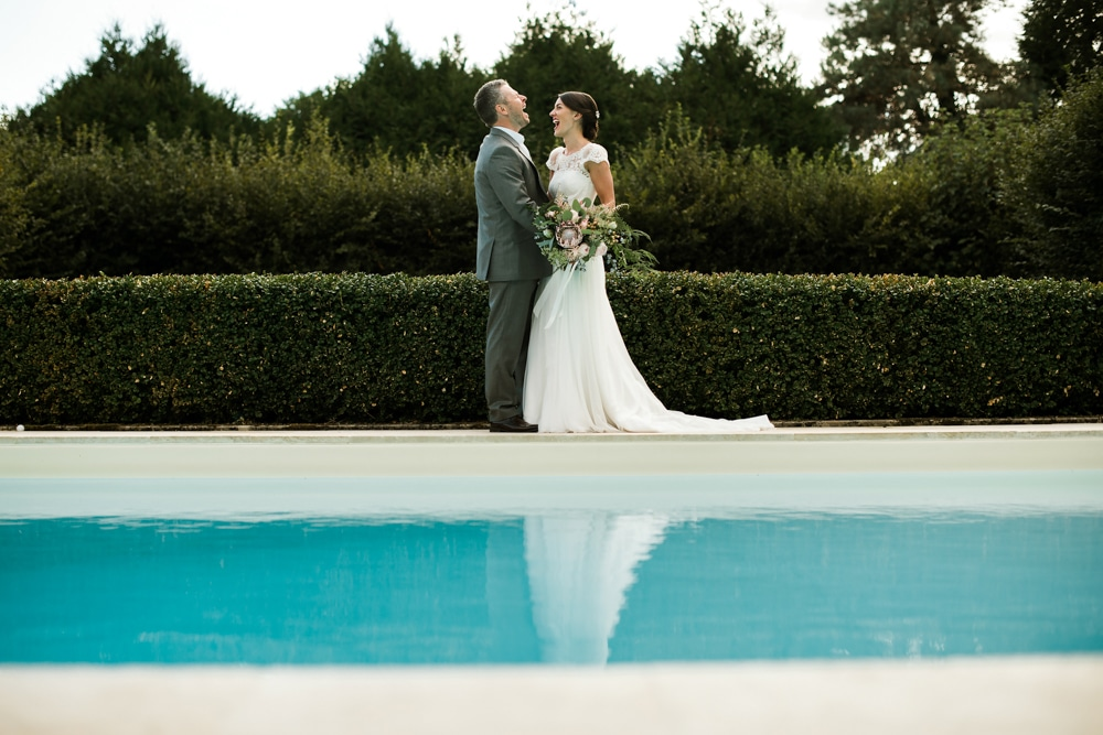 wedding day portraits of bride and groom around swimming pool