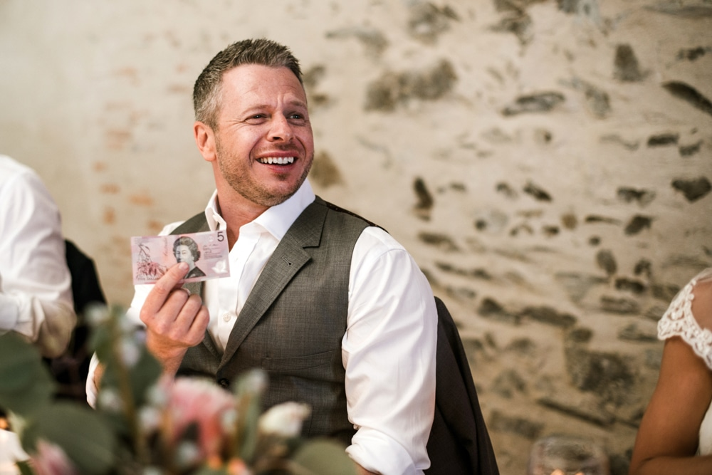 groom holding up bank note
