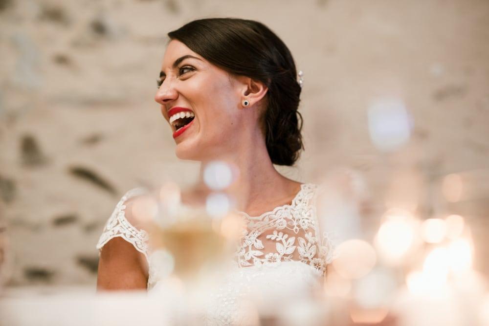 bride shot through wine glasses during wedding speeches
