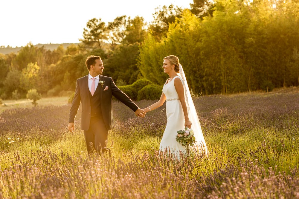 bride and groom walking through lavender in France