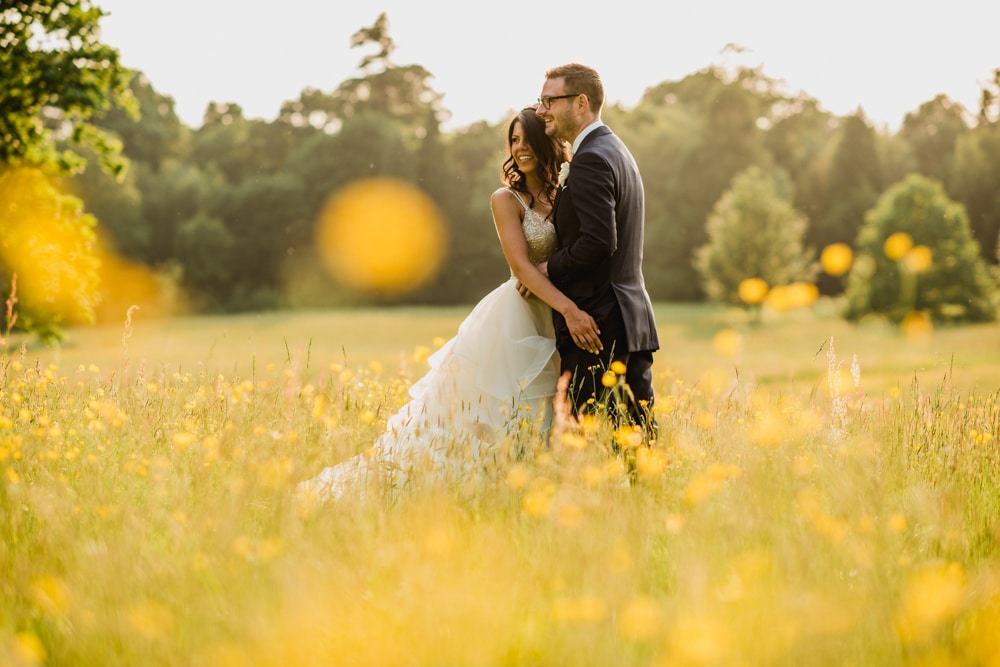 bride and groom in Buttercup field