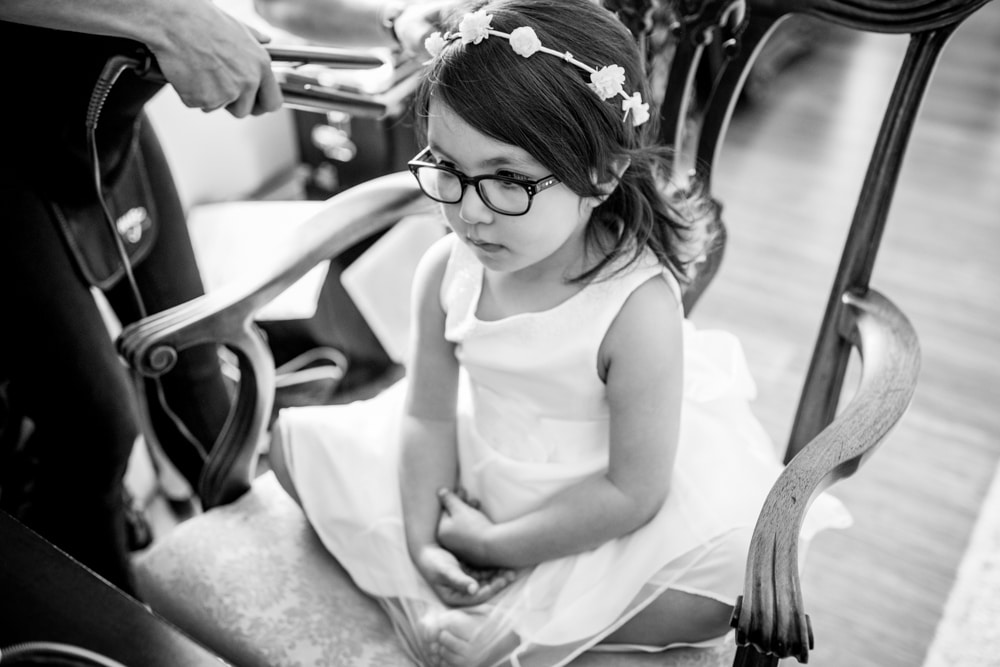 flower girl getting her hair done at wedding