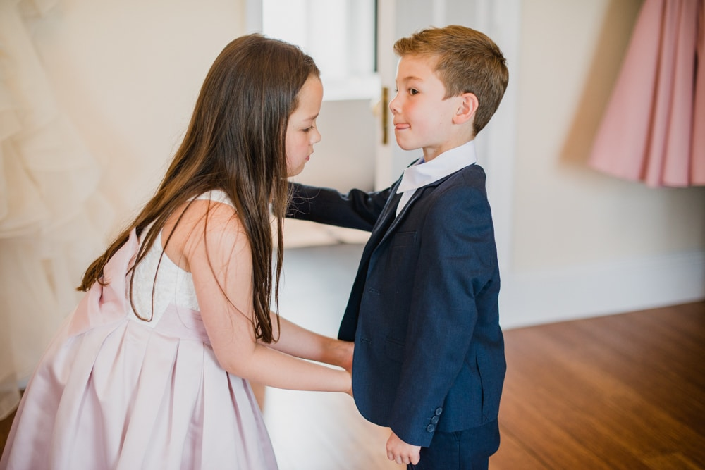 flower girl helping pageboy get ready