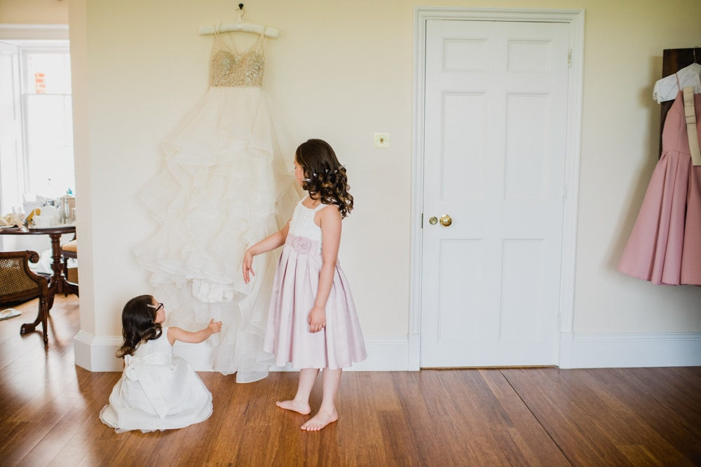 flower girls looking at wedding dress